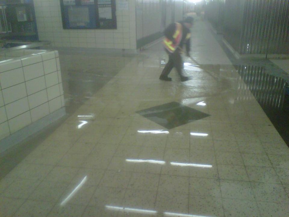 A worker mops up water left inside Bloor-Yonge Station following a water main break early Saturday morning. (Twitter/TTC)