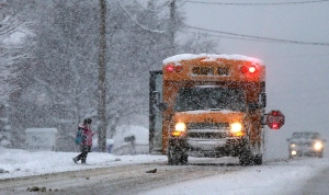 A youngster makes her way onto a school bus in Holland, N.Y., on Wednesday, Dec. 11, 2013. (AP Photo/The Buffalo News, Robert Kirkham)