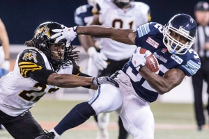 Toronto Argonauts' Andre Durie, right, catches a pass for a first down despite pressure from Hamilton Tiger-Cats player Courtney Stephen during the CFL eastern conference final in Toronto on Sunday, Nov. 17, 2013. (The Canadian Press/Chris Young)