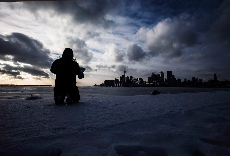 Joanna Leung takes pictures of the skyline and a frozen Lake Ontario during sub-freezing weather in Toronto on Tuesday, Jan. 7, 2014. (The Canadian Press/Mark Blinch)