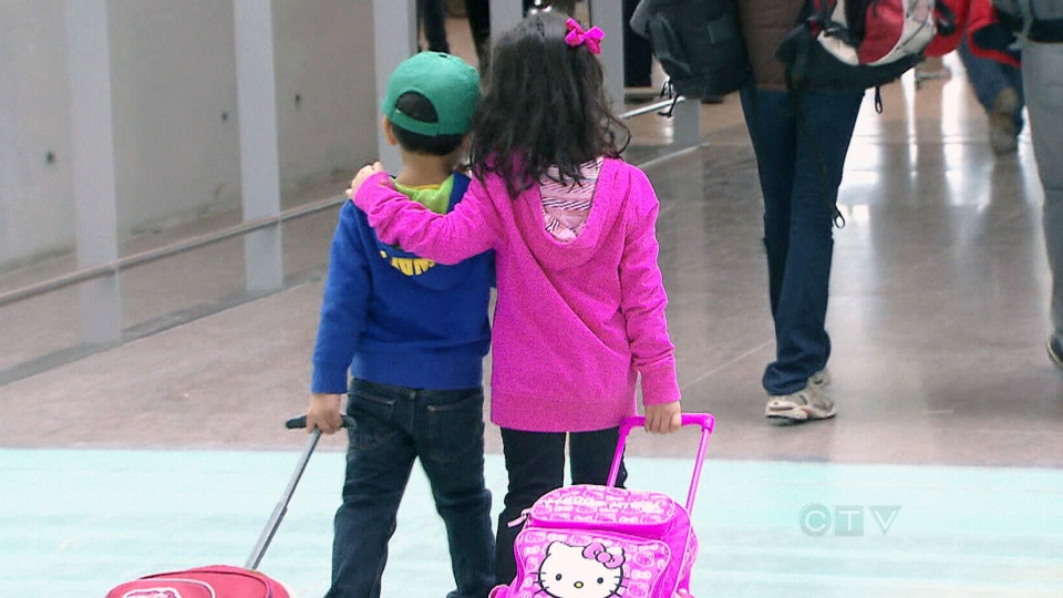 Children are seen pulling luggage in an undated file photo.