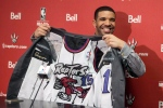 Hip Hop Star Drake shows off the lining of his suit during a press conference before the Toronto Raptors' NBA game against Brooklyn Nets in Toronto on Saturday Jan. 11 , 2014.(Chris Young /The Canadian Press)