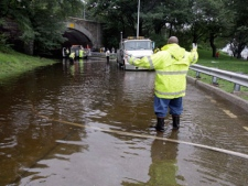 Workers from New York City's Dept. of Environmental Protection pump water from a flooded exit of New York's West Side Highway, Sunday, Aug. 28, 2011. Tropical storm Irene weakened after landfall over the North Carolina coast Saturday, but it was still a massive storm with sustained winds of up to 65 mph as it hit the city. (AP Photo/Richard Drew)
