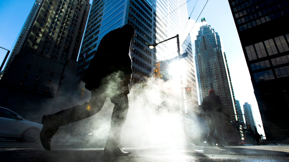 A man makes his way through the cold in the city's financial district in downtown Toronto on Tuesday, Jan. 28, 2014. (The Canadian Press/Nathan Denette)