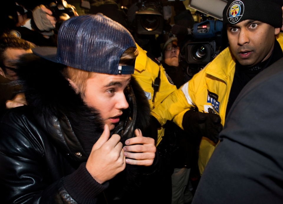 Pop star Justin Bieber is swarmed by media and police officers outside a police station in Toronto on Wednesday, Jan. 29, 2014. (The Canadian Press/Nathan Denette)