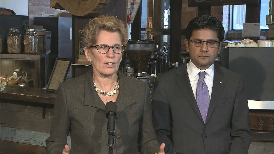 Ontario Premier Kathleen Wynne speaks to reporters as Labour Minister Yasir Naqvi listens Thursday, Jan. 30, 2014.