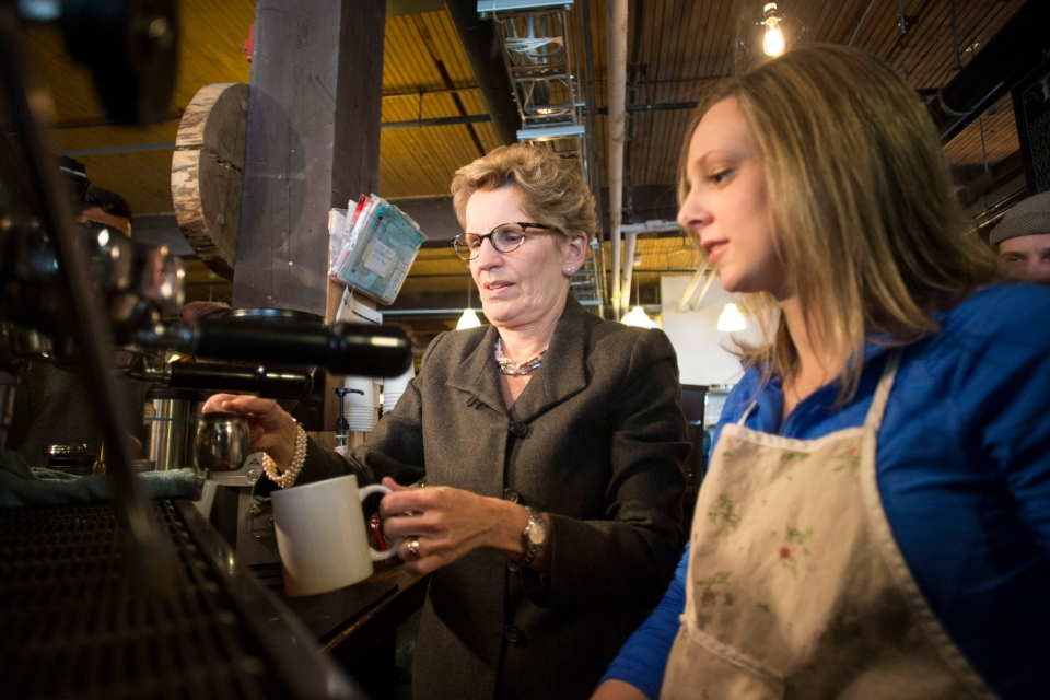 Ontario Premier Kathleen Wynne (left) is shown how to brew a cup of coffee at 'The Coffee Pub' by owner Erin Cluley, on Thursday, January 30, 2014. The premier announced Ontario's minimum wage will be increased to $11 an hour effective June 1, up 75 cents. (Chris Young/The Canadian Press)