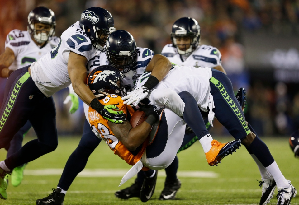 Denver Broncos' Demaryius Thomas (88) is tackled by Seattle Seahawks' K.J. Wright (50), Bobby Wagner (54) and Mike Morgan after making a reception during the first half of the NFL Super Bowl XLVIII football game Sunday, Feb. 2, 2014, in East Rutherford, N.J. (AP /Jeff Roberson)
