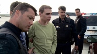 Luka Rocco Magnotta is taken by police from a Canadian military plane to a waiting van in Mirabel, Que., on Monday, June 18, 2012. (Montreal Police)