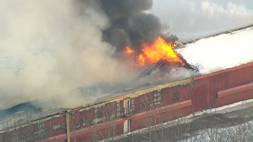 Flames shoot through the roof of a barn at a chicken farm near Aurora on Thursday, Feb. 13, 2014.