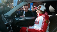 Russian Prime Minister Dmitry Medvedev, rear, speaks with Russian Olympic champion in figure skating Julia Lipnitskaia, sitting in her new Mercedes-Benz in Red Square in Moscow, Thursday, Feb. 27, 2014. (AP Photo/RIA-Novosti, Yekaterina Shtukina, Government Press Service)