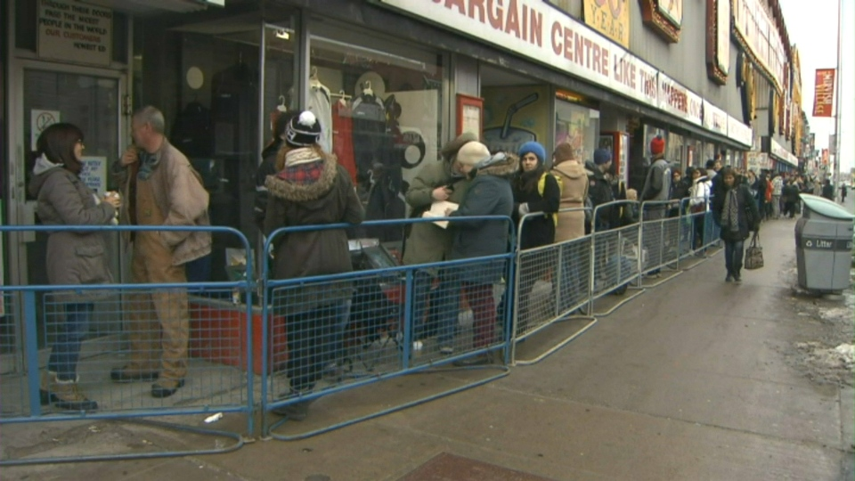 People line up outside Honest Ed's on Monday, March 10, 2014, before the iconic store sold off some of its wacky and colourful signs.