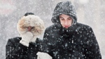 A couple shields themselves from blowing snow on Clifton Hill in Niagara Falls, Ont., during a snow storm Wednesday, March 12, 2014. THE CANADIAN PRESS/Aaron Lynett