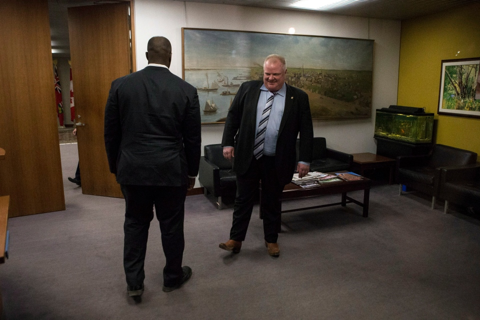 Toronto Mayor Rob Ford, right, steps out of his office after speaking to a group of students Wednesday, March 19, 2014. (The Canadian Press/Chris Young)