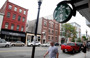 The logo on a new Starbucks is seen across the street from the building, left, which once housed the Triple O's bar in Boston on Thursday, June 6, 2013. (AP Photo/Michael Dwyer)