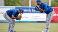 Toronto Blue Jays infielder Munenori Kawasaki, left, and right fielder Jose Bautista bow to each other after going through Kawasaki's exercise regimen together prior to a spring exhibition baseball game in Tampa, Fla., on Sunday, March 23, 2014. (AP Photo/Kathy Willens)
