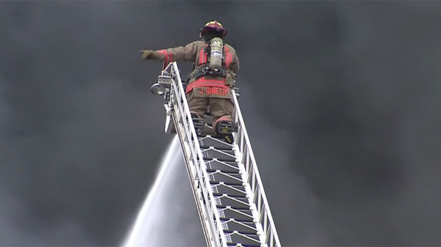 A firefighter stands on a ladder and directs water onto hot spots at a massive mattress factory blaze in the Dufferin Street and Eglinton Avenue area Thursday March 27, 2013.