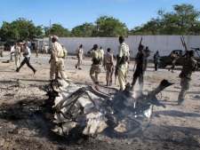 Somali government forces attend the scene of a car bomb in Mogadishu, Somalia Tuesday, Oct. 18, 2011. A suicide car bomb exploded near Somalia's Foreign Ministry on Tuesday, killing at least four people including the bomber, a police official said, on the same day that Kenya's ministers of defense and foreign affairs are in Mogadishu to meet with government leaders after Kenya on Sunday launched military operations in southern Somalia against al-Shabab militants. (AP Photo/Mohamed Sheikh Nor)