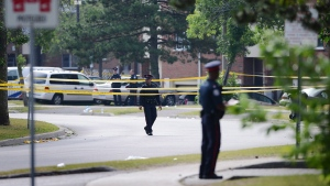 Police stand on guard on Danzig Street on Tuesday, July 17, 2012 following a mass shooting at a community barbecue. The city will introduce a new program geared towards helping communities heal in the wake of violent crimes, Mayor Tory announced on June 30, 2016. (The Canadian Press/Aaron Vincent Elkaim)