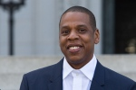 Jay Z, also known as Shawn Carter, smiles during a press conference for the Made in America Festival at City Hall on Wednesday, April 16, 2014 in Los Angeles. (Photo by Paul A. Hebert/Invision/AP)