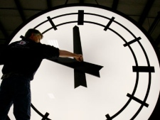 Electric Time machinist Scott Gow prepares to remove the hands of an eight-foot clock at the Electric Clock factory in Medfield Mass., March 9, 2007. (AP Photo/Stephan Savoia)