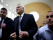Former Israeli President Moshe Katsav, center, pauses at the Supreme court in Jerusalem, Thursday, Nov. 10, 2011. Israel's Supreme Court on Thursday ordered former President Moshe Katsav to spend seven years in prison after rejecting the disgraced politician's appeal of a rape conviction and other sex crimes. (AP Photo/Uriel Sinai)