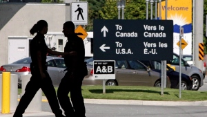 Canadian border guards are silhouetted as they replace each at the Douglas border crossing in Surrey, B.C., on Aug. 20, 2009. (The Canadian Press/Darryl Dyck)