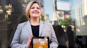 NDP leader Andrea Horwath shows off her party's new financial savings app as she talks with the media after a campaign stop in Toronto on Monday, June 2, 2014. THE CANADIAN PRESS/Nathan Denette
