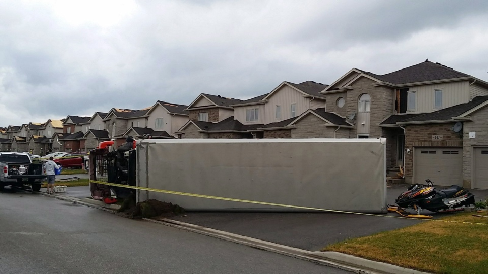 An overturned truck sits in the driveway of a storm damaged house in Angus, near Barrie, Ontario on Tuesday, June 17, 2014. (The Canadian Press/Christopher Bentley)