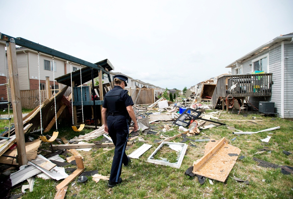 An OPP officer assesses the damage to homes and property on Wednesday, June 18, 2014, a day after a tornado touched down in Angus, Ont. (The Canadian Press/Nathan Denette)