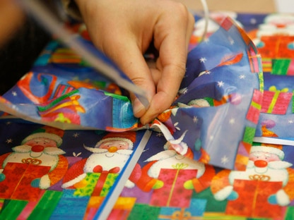 A person wraps a Christmas gift in this file photo. (AP Photo/Thomas Kienzle, file)