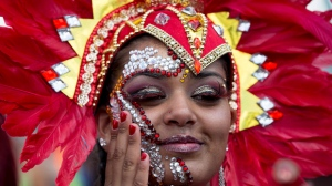 A parader checks on her jewels during the Caribbean Carnival in Toronto on Saturday, August 3, 2013. THE CANADIAN PRESS/Michelle Siu