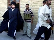 In this June 5, 2004 file photo, Shiite cleric Muqtada al-Sadr, left, steps from an office building in Najaf, Iraq. The political party loyal to radical Shiite cleric Muqtada al-Sadr called Monday Dec.26 2011 for the dissolution of Iraq's parliament and new elections in another move that could escalate the country's growing sectarian crisis. (AP Photo/Khalid Mohammed)