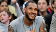 In this Jan. 24, 2014 file photo, New York Knicks player Carmelo Anthony smiles as he watches from the bench during the fourth quarter of an NBA game against the Charlotte Bobcats at Madison Square Garden in New York. (AP Photo/Bill Kostroun, File)