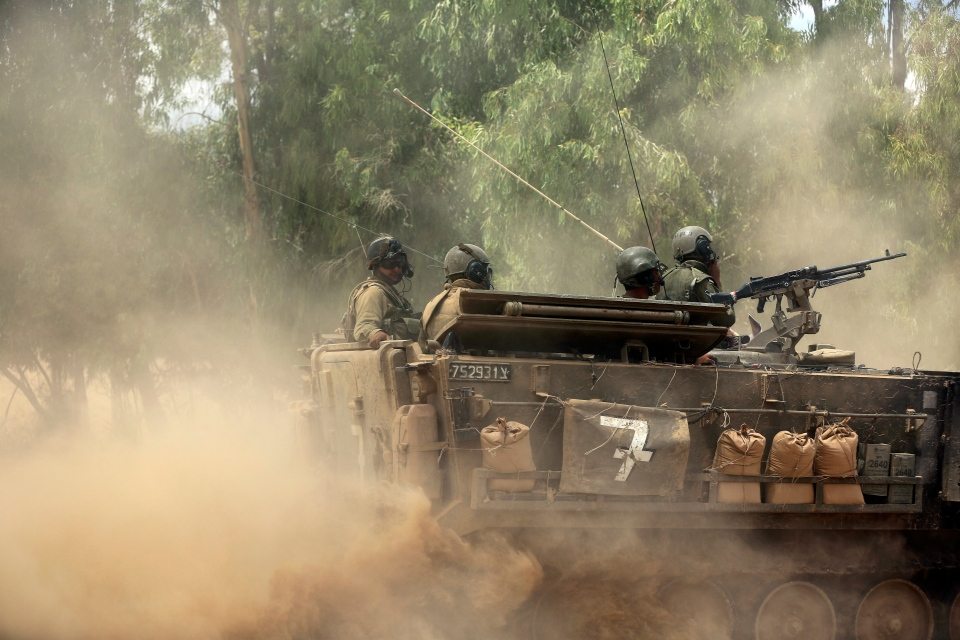Israeli soldiers ride near the border with Gaza, Saturday, July 19, 2014. Israel pounded Hamas rocket launchers and uncovered more than a dozen cross-border tunnels. (AP Photo/Tsafrir Abayov)