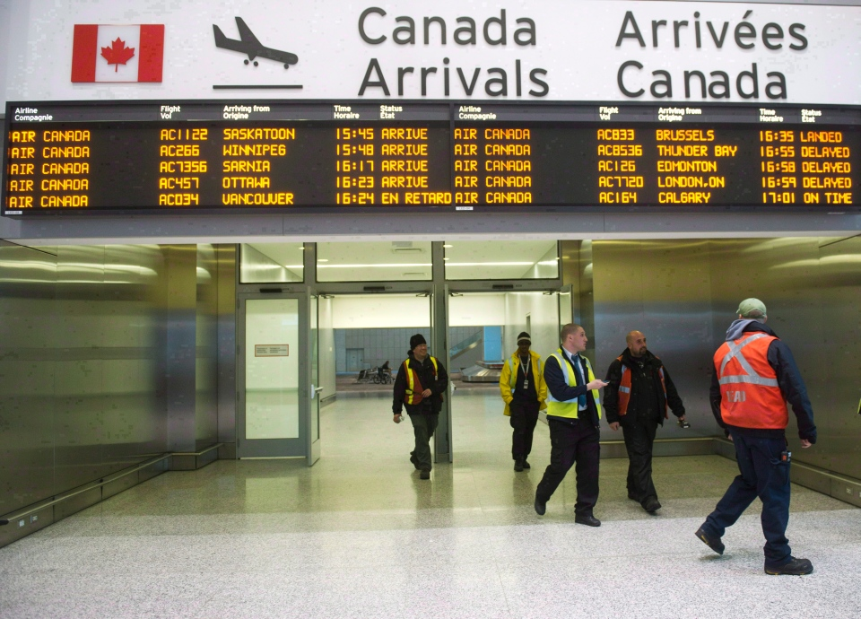 Air Canada workers walk at Pearson International Airport in Toronto on March. 8, 2012. (Nathan Denette/ The Canadian Press)