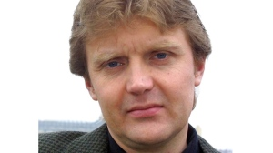 """FILE - In this Friday, May 10, 2002 file photo Alexander Litvinenko, former KGB spy and author of the book """"Blowing Up Russia: Terror From Within"""", is photographed at his home in London. The British government Tuesday, July 22, 2014 announced plans for a wide-ranging public inquiry into the 2006 death of poisoned ex-Russian spy Litvinenko. The decision, which comes at a time of rising tensions with Russia, means investigators can look into whether the Russian state played a role in Litvinenko's demise. (AP Photo/Alistair Fuller, File)"""