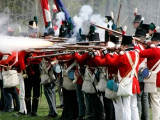 British soldiers fire their muskets at the American forces during a re-staging of the War of 1812 skirmish between American and British forces near the actual battle site west of London, Ontario Saturday May 5, 2007. The Harper government has hired a theatre expert to add a dash of war to the annual Canada Day celebrations on Parliament Hill this summer. THE CANADIAN PRESS/Dave Chidley
