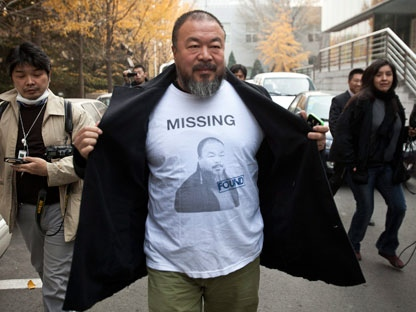 In this Nov. 16, 2011 photo, Chinese dissident artist Ai Weiwei opens his jacket to reveal a shirt bearing his portrait as he walks into the Beijing Local Taxation Bureau. (AP Photo/Andy Wong)