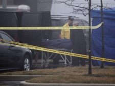 A body is carried away from a crime scene outside an Oakville police station on Oak Walk Drive on Jan. 12, 2012.