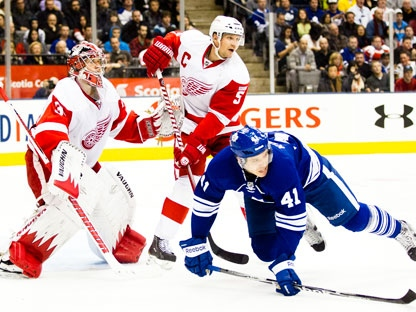 Toronto Maple Leafs left winger Nikolai Kulemin (41) is tripped up by Detroit Red Wings defenceman Nicklas Lidstrom in front of goaltender Jimmy Howard (35) during second period NHL action in Toronto on Saturday January 7, 2012. THE CANADIAN PRESS/Frank Gunn