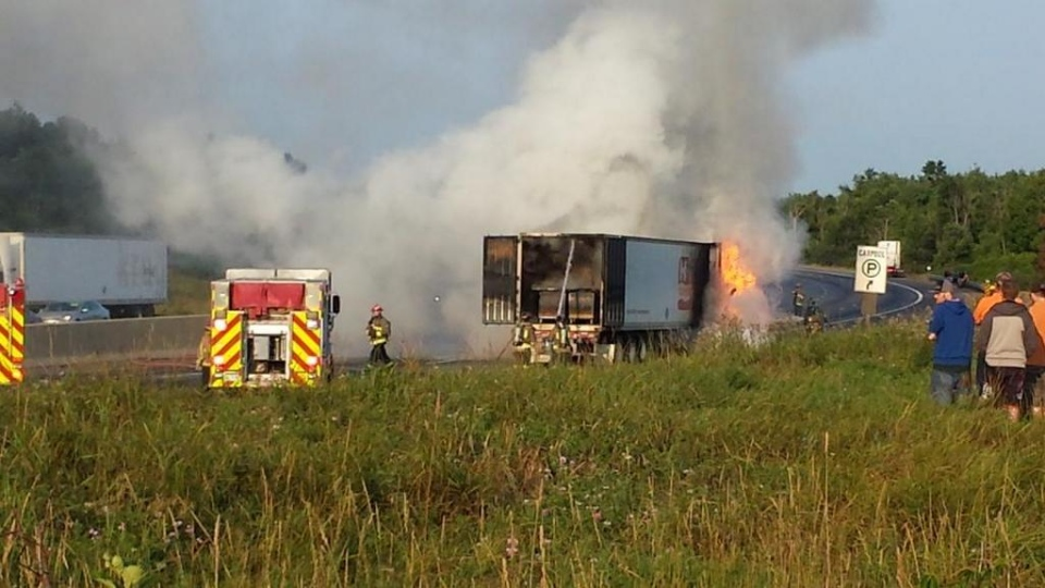 Firefighters work to extinguish a blaze after a tractor trailer carrying cheese burst into flames on the westbound lanes of highway 401 in Milton Thursday, Aug. 7, 2014. (@WilcoxBodies /Twitter)