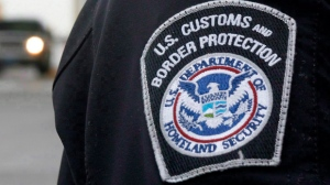 A U.S. Customs and Border Protection (CMP) officer stands near a security booth as vehicles approach in Detroit, Michigan, on June 1, 2009. (Dave Chidley/The Canadian Press)
