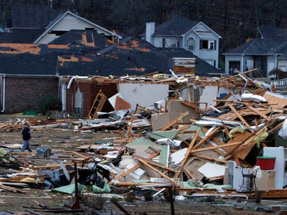 Residents walk around through debris after a possible tornado ripped through the Trussville, Ala., area in the early hours of Monday, Jan. 23, 2012. (AP Photo/Butch Dill)