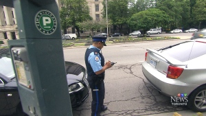 A Toronto parking enforcement officer checks a license plate of a vehicle in an undated file image.