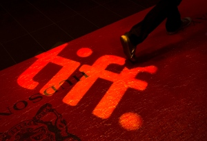 A man walks on a red carpet displaying a sign for the Toronto International Film Festival at the TIFF Bell Lightbox in Toronto on Wednesday, Sept. 3, 2014. (The Canadian Press/Darren Calabrese)