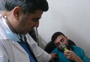 In this file image taken from video obtained from the Shaam News Network, posted on April 18, 2014, an anti-Bashar Assad activist group, which has been authenticated based on its contents and other AP reporting, a Syrian man is seen receiving oxygen from a medic in Kfar Zeita, a rebel-held village in Hama province some 200 kilometers (125 miles) north of Damascus. (AP Photo/Shaam News Network)