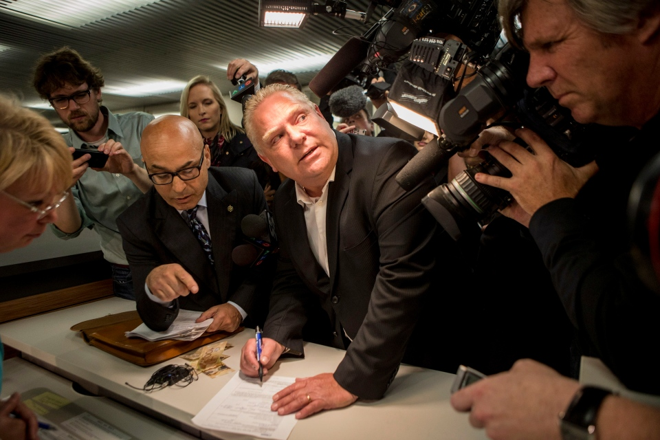 Doug Ford tries to avoid the glare of a television camera as he submits his papers in Toronto on Friday, September12, 2014 to enter the mayoral race after the withdrawal of Rob Ford. THE CANADIAN PRESS/Chris Young