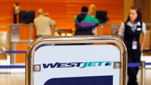 A host waits to direct passengers at a Westjet Airlines check-in counter at Calgary Airport. (The Canadian Press/Larry MacDougal)