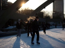 Skaters' breath is lit by the setting sun while skating on a cold afternoon in Toronto, Ont. Sunday, January 23, 2011. THE CANADIAN PRESS/Darren Calabrese